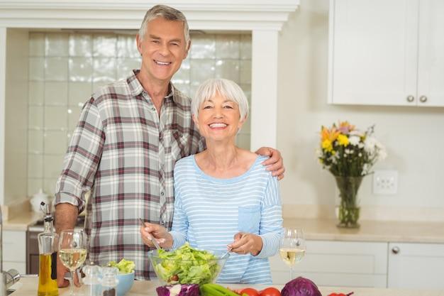 Coppie senior che preparano insalata di verdure