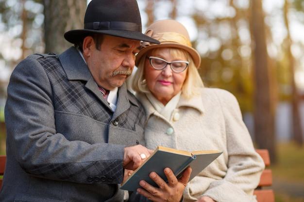 Coppie senior che leggono insieme un libro nel parco di autunno