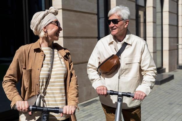 Coppia senior in sella a uno scooter elettrico in città