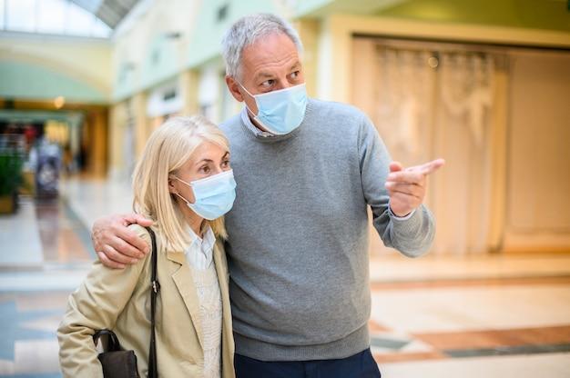 Coppia senior shopping in un centro commerciale a volte coronavirus, indossando maschere