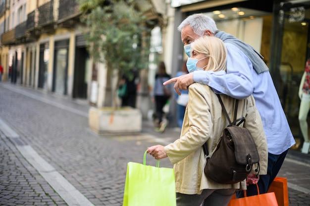 Coppia senior shopping all'aperto ai tempi di coronavirus, indossando maschere