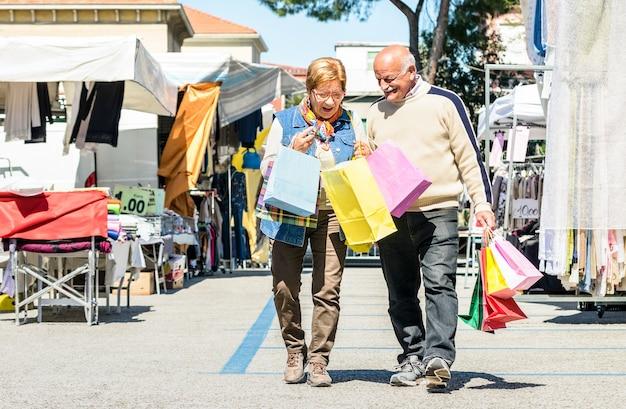 Coppia senior shopping insieme al mercato delle pulci con la moglie guardando in borse del marito - concetto di anziani attivi con uomo maturo e donna che si diverte in città - momenti di pensionati felici su colori vivaci