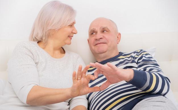 Coppia senior che mostra il gesto del cuore della mano. relazioni, amore e concetto di persone anziane.