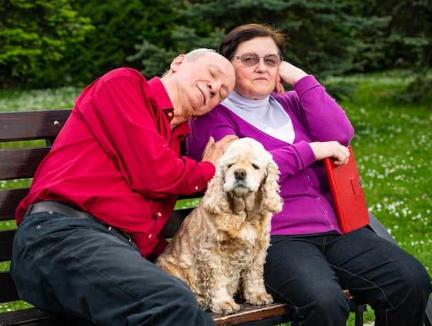 Coppia senior seduta su una panchina e godersi la primavera nel parco