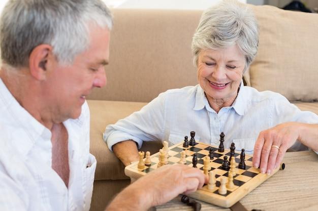 Coppie senior che si siedono sul pavimento che gioca scacchi