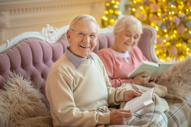Coppia senior seduto su un divano e leggere libri