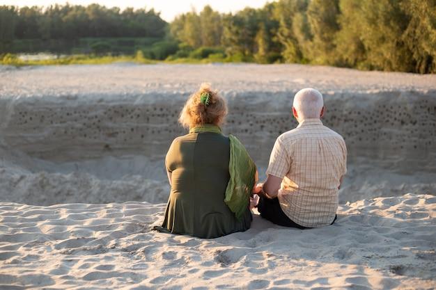 Coppie senior che si siedono insieme in spiaggia di estate