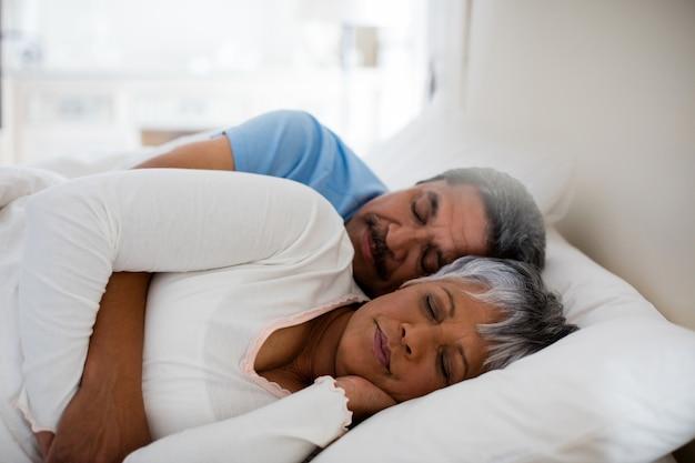Coppie senior che dormono insieme sul letto in camera da letto