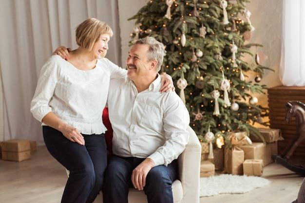 Coppia senior sorridente accanto al loro albero di natale a casa in soggiorno