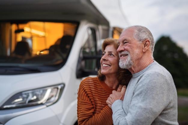 Una coppia di anziani in piedi e abbracciati all'aperto al tramonto, viaggio di vacanza in roulotte.
