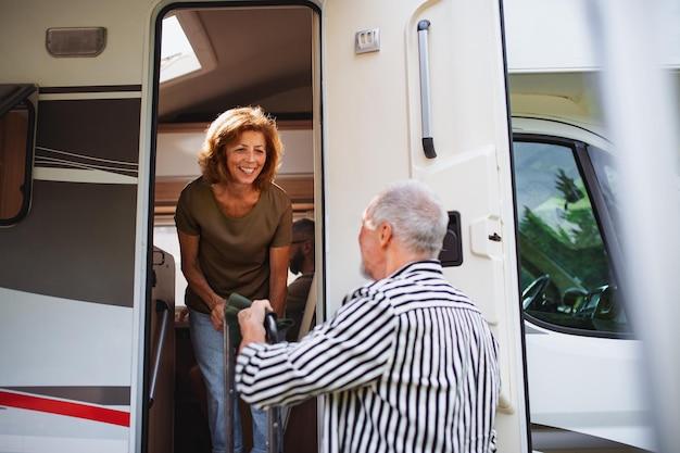 Coppia anziana che disimballa e parla in auto, viaggio di vacanza in roulotte con la famiglia.