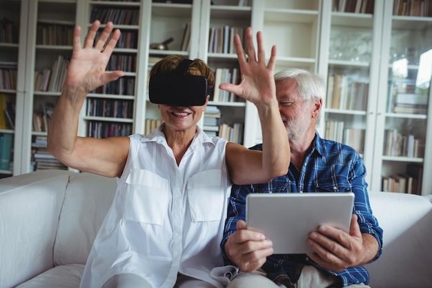 Coppie senior facendo uso della compressa digitale e della cuffia avricolare di realtà virtuale