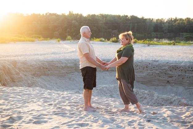 Le coppie senior su una passeggiata nella natura dell'estate, coppia senior si rilassano nell'ora legale di primavera.