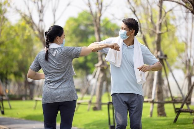 Coppia senior indossando la maschera per il viso e camminando attraverso il parco naturale, allenamento estivo all'aperto