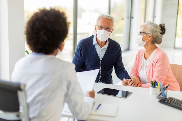Coppia senior con maschere facciali protettive riceve notizie da dottoressa nera in ufficio