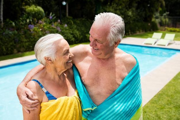 Coppia senior avvolta in un asciugamano a bordo piscina