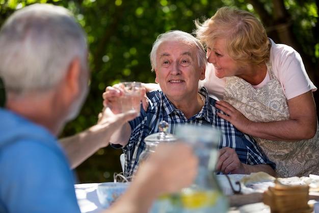 Coppie senior che mangiano prima colazione in giardino