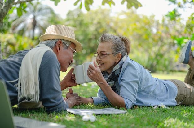 Anziano, coppie, pensione, assicurazione, anziani, concetto di stile di vita. le coppie anziane bevono caffè sul prato all'aperto al mattino sui piani di assicurazione sulla vita con una felice pensione.