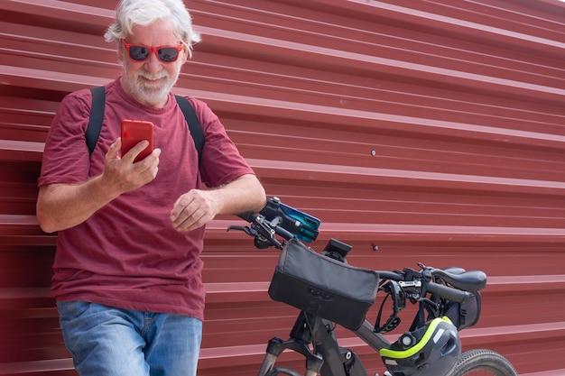 Ciclista senior in escursione urbana della città con la bicicletta elettrica facendo uso del telefono cellulare che sorride