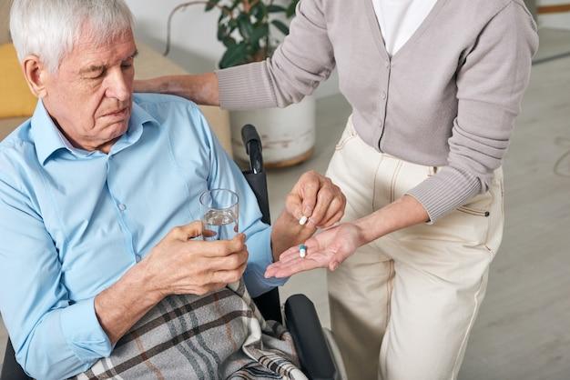 Uomo anziano disabile con bicchiere d'acqua prendendo pillole dalla mano di sua figlia o assistente sociale aiutandolo con la routine quotidiana