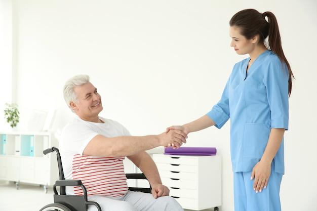 Anziano disabile con giovane ortopedico in clinica di riabilitazione