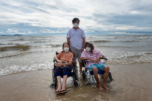 Senior persona disabile in sedia a rotelle in spiaggia contro lo sfondo del tramonto.