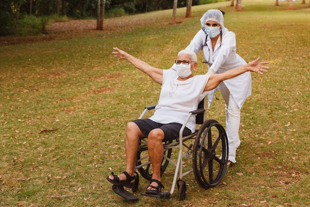 Senior donna disabile con badante nel giardino della casa di cura