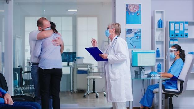 Medico senior che dà cattive notizie a una giovane coppia nell'area di attesa dell'ospedale. medico in camice bianco che indossa una maschera facciale contro l'infezione da coronavirus. infermiera con visiera.