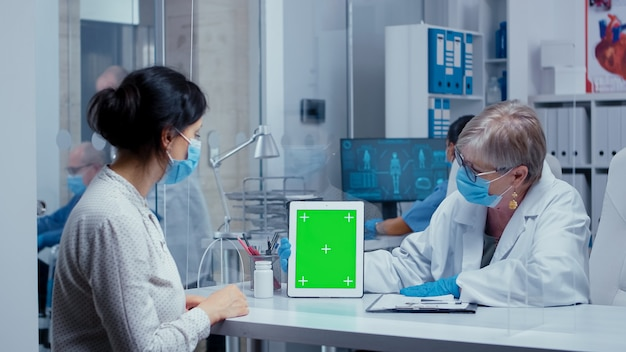 Medico anziano in possesso di uno schermo verde presentato durante la crisi sanitaria covid-19, che mostra informazioni al paziente, indossando maschera e guanti di protezione. consultazione medica nel concetto di equipaggiamento protettivo colpo di sar