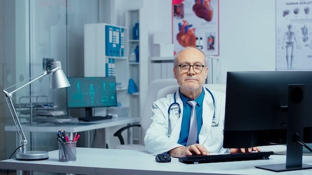 Medico senior in una clinica privata moderna che lavora al pc e poi sorride alla telecamera. medico specialista in medicina in uniforme che lavora in ospedale con personale numeroso