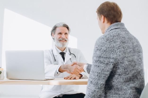 Medico senior che stringe le mani con il paziente mentre incontrandosi all'ambulatorio.