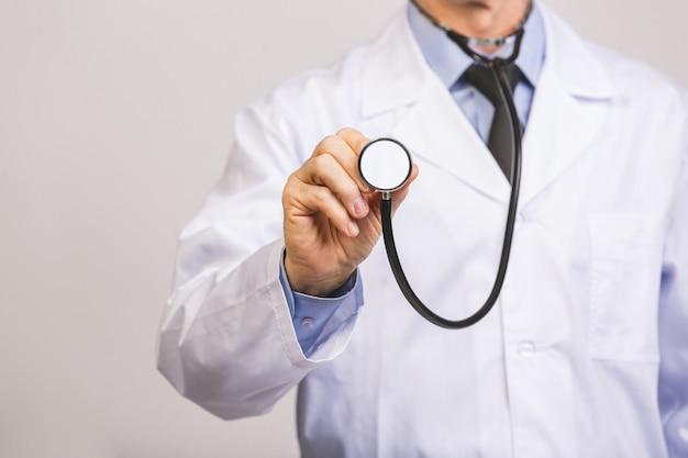 Il medico senior utilizza lo stetoscopio del fonendoscopio isolato su una parete grigia.