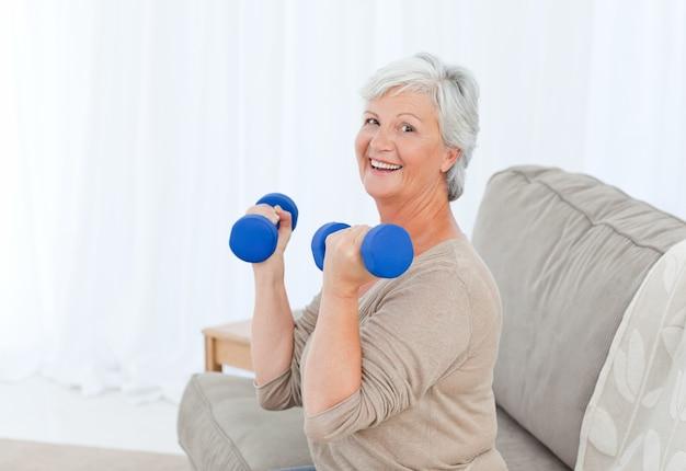 Senior facendo i suoi esercizi sul suo divano