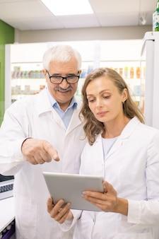 Proprietario senior di una farmacia che punta allo schermo del touchpad mentre mostra al suo giovane assistente una nuova medicina nella base del computer