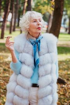 Senior elegante elegante donna alla moda con i capelli grigi in pelliccia sigaretta fumatori all'aperto