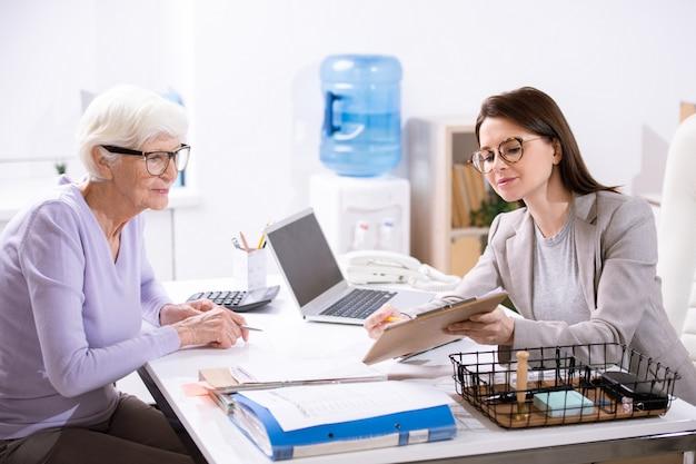 Senior donna elegante guardando il modulo di assicurazione mentre giovane agente femminile che punta a uno dei punti e lo spiega
