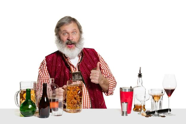 Il barista maschio esperto senior con birra isolato sul muro bianco. giornata internazionale del barman, bar, alcol, ristorante, birra, festa, pub, concetto di celebrazione del giorno di san patrizio