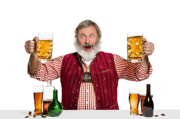 Il barman maschio esperto senior con birra a isolato sulla parete bianca. giornata internazionale del barman, bar, alcol, ristorante, birra, festa, pub, concetto di celebrazione del giorno di san patrizio