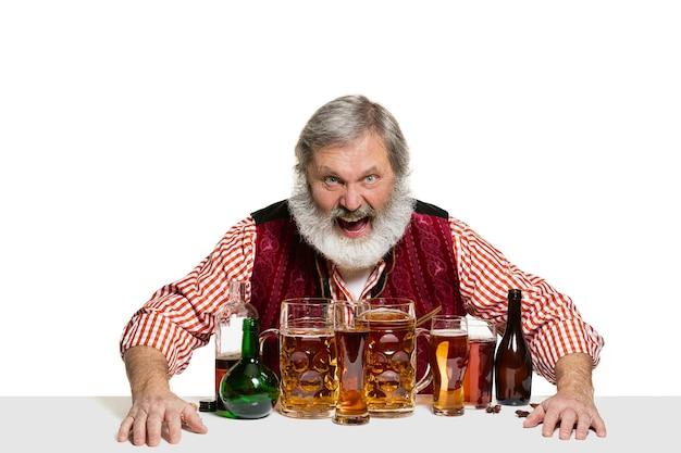 Il barman maschio esperto senior con birra in studio isolato su parete bianca
