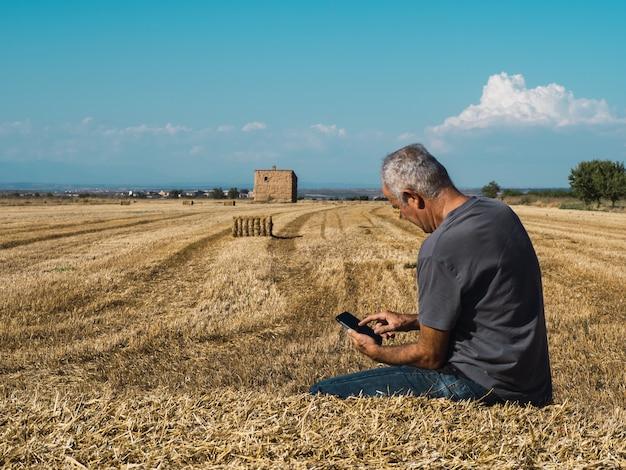 Agricoltore senior che si siede sulla balla di paglia che esamina il telefono cellulare nel concetto di agricoltura del campo