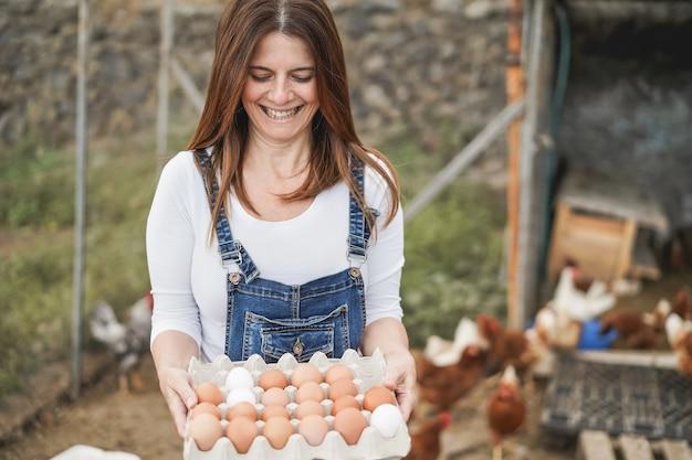 Donna agricoltrice anziana che raccoglie uova biologiche nel pollaio - focus sul viso