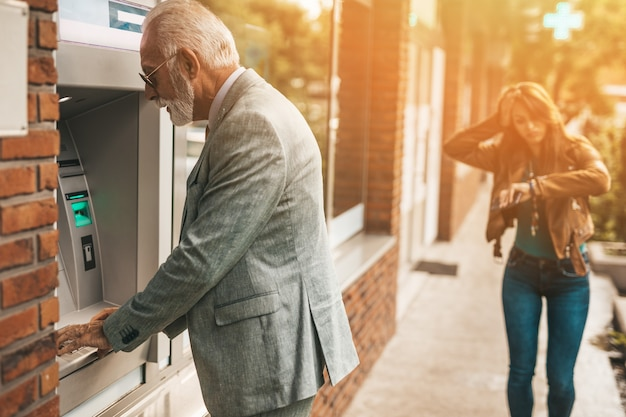 Padre anziano e sua figlia che usano insieme il bancomat per prelevare denaro. loro sono felici. luminosa giornata di sole.
