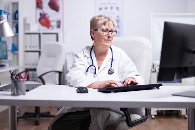 Dottoressa anziana in camice da laboratorio, occhiali e stetoscopio sul collo digitando sul computer seduto in studio medico utilizzando guardando il desktop sorridente mentre si lavora in studio medico