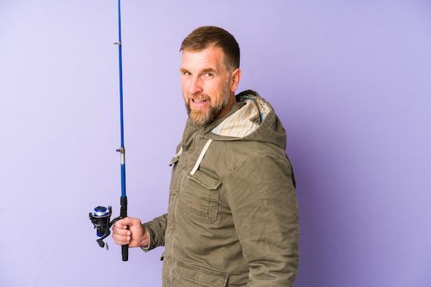 Il pescatore senior isolato su sfondo viola sembra da parte sorridente, allegro e piacevole.