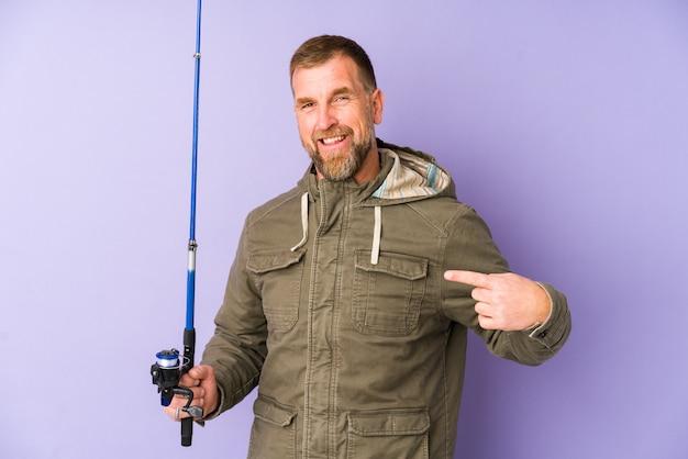 Pescatore senior isolato sulla persona porpora che indica a mano uno spazio della copia della camicia, fiero e sicuro