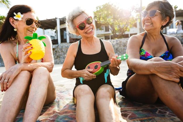 Amici anziani che si divertono in spiaggia