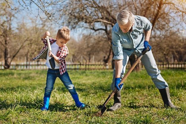 Un giardiniere anziano e suo nipote all'aperto trascorrono del tempo libero insieme mentre piantano nuovi alberi da frutto nel cortile