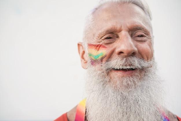 Senior gay uomo sorridente durante la protesta di orgoglio lgbt - focus sul viso