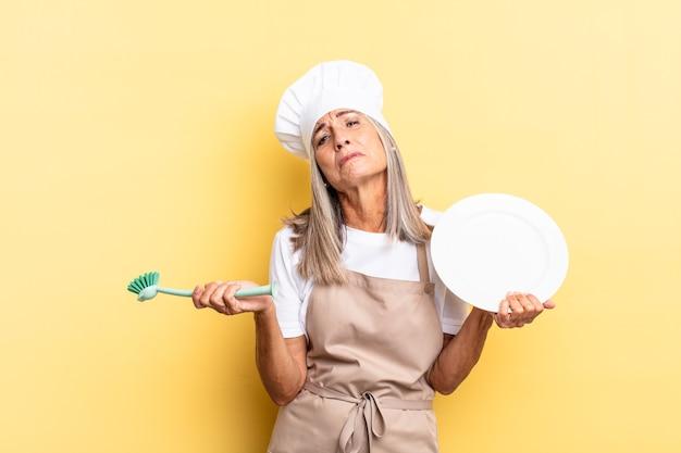 Donna anziana dei capelli grigi. concetto di lavaggio dei piatti