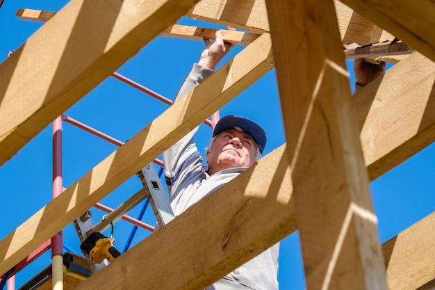 Il costruttore senior dai capelli grigi raccoglie il telaio di una casa di campagna in legno